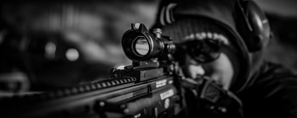 man looks through scope on rifle