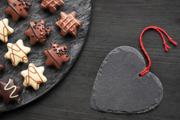 Star-shaped chocolates on dark textured background with black heart