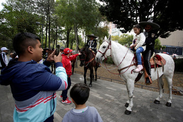 A girl poses for a picture with a Mexico City's mounted police officer on horseback at the Alameda Central in downtown Mexico City