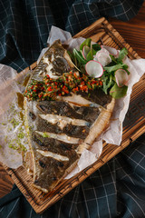 High angle view of roasted fish served on wooden tray