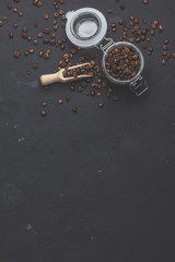 Glass jar with roasted beans on black stone concrete surface