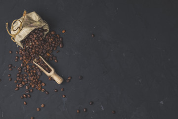 Purse with roasted beans and wooden scoop on black stone concrete textured surface