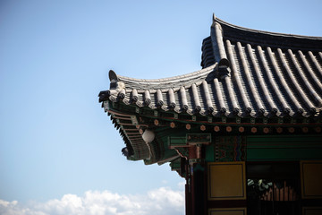 Low angle view of Buddhist temple roof against blue sky during sunny day