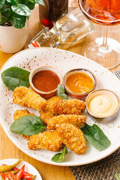 High angle view of chicken nuggets served with basil leaves and various sauces in white plate on table