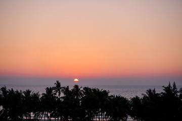 Sunset at the burmese ocean with palms