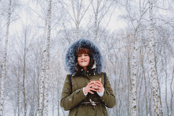 Low angle portrait of woman holding tea while standing against trees in park during winter