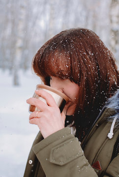 Close-up of woman drinking tea while standing in park during snowfall