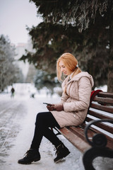 Woman using mobile phone while sitting on bench against trees in park during winter
