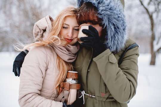 Lesbian couple having drink while standing in park during winter