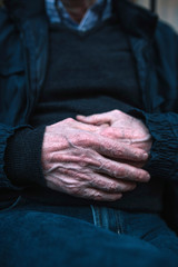 Midsection of senior man wearing warm clothing with hands clasped sitting outdoors