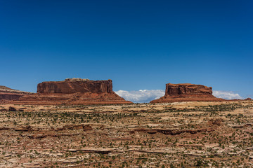 Scenic view of arid landscape against blue sky during sunny day