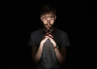 Portrait of confident thoughtful man with beard standing against black background