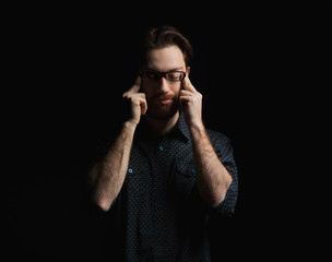 Confident man with eyes closed meditating while standing against black background