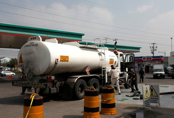 A tanker truck delivers fuel at a gas station, in Mexico City