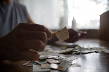Close-up of man holding postage stamps with tweezers on table at home