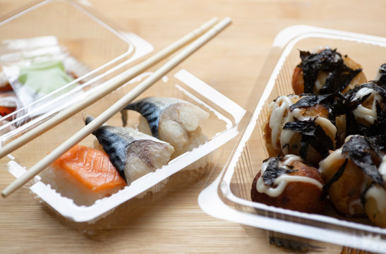 Close-up of seafood with shopsticks in plastic containers on table