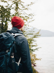 Side view of backpacker looking at lake while standing in forest