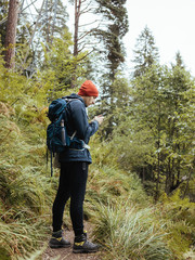 Side view of backpacker using mobile phone while standing in forest