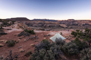 Tent on arid landscape against clear sky at Canyonlands National Park during sunset