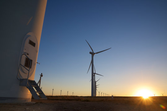 Surface level image of silhouette windmills on landscape against clear blue sky during sunset