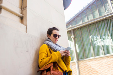 Female tourist wearing warm clothing and sunglasses using smart phone while standing against wall