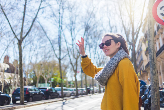 Side view of fashionable female tourist wearing warm clothing hitchhiking while standing in city during sunny day