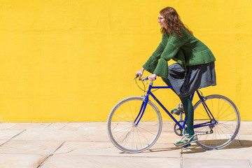 Side view of businesswoman riding bicycle on sidewalk against yellow wall during sunny day
