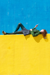 Side view of businesswoman using smart phone while lying on yellow wall during sunny day