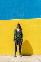 Portrait of confident businesswoman standing on sidewalk against colorful wall during sunny day