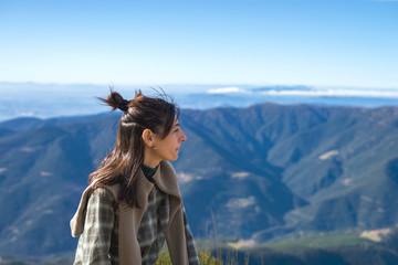 Woman looking at view while sitting on mountain against clear blue sky during sunny day