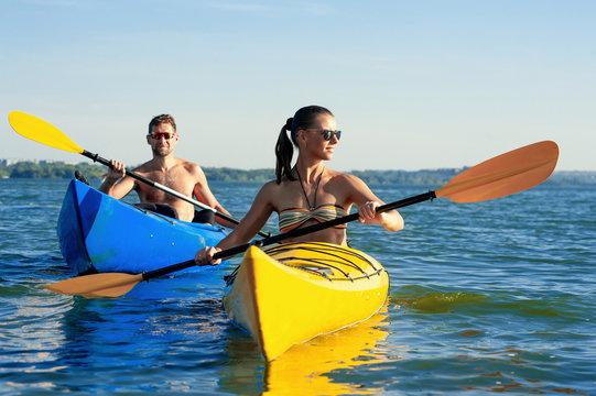 Couple kayaking together enjoying summer day on the lake