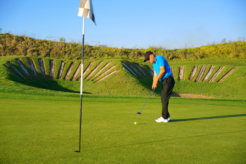 Golf player is swinging at links golf course