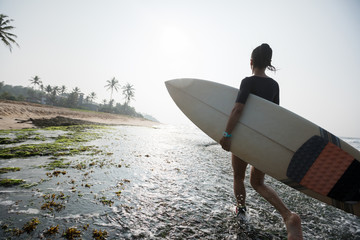 Woman surfer walking with surfboard on mossy coral reefs