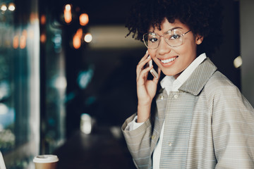 Cheerful lady looking at camera and speaking on phone
