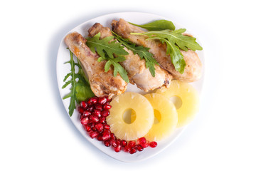 Fried chicken legs with rucola, pineapple and pomegranate seeds isolated on white background.