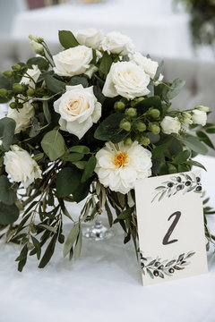 Wedding decor. Beautiful bouquet of blooming white roses and peonies, and greenery, on the table. Nearby there is a plate number of the table