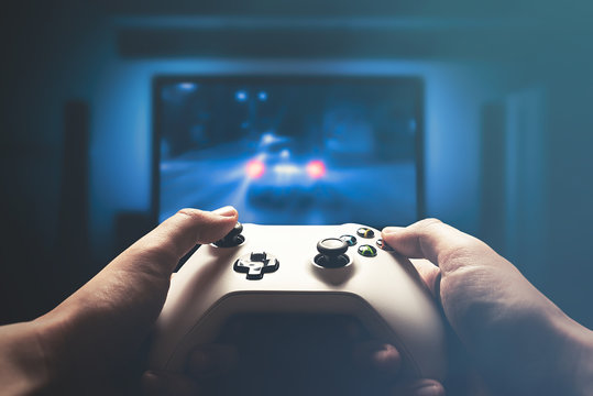Video gaming console. Man playing car racing