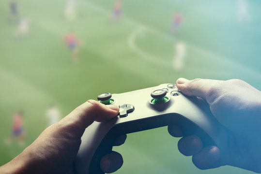 Video gaming console. Man playing soccer game
