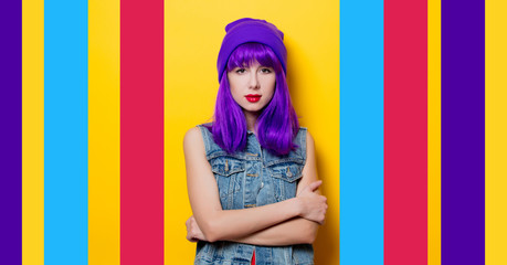 Portrait of young style hipster girl with purple hair on yellow background