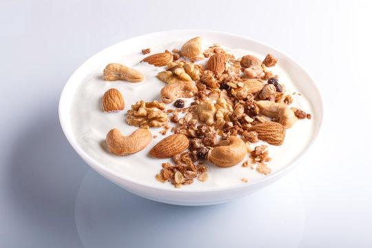 White plate with greek yogurt, granola, almond, cashew, walnuts isolated on white background.