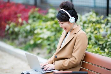 パソコンで音楽を聴く女性