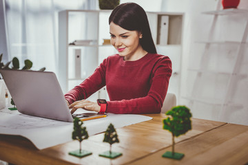 Cheerful positive woman being at work