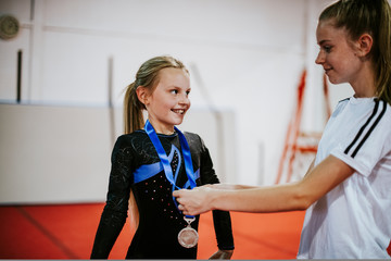 Coach giving a silver medal to a young gymnast