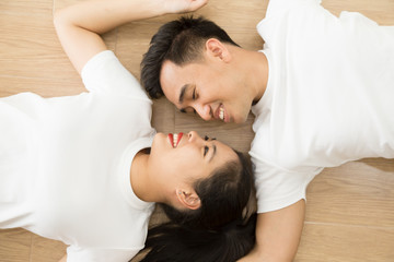 Asian couple looking at each other and lying on the floor at home, True love and Prewedding photography concept