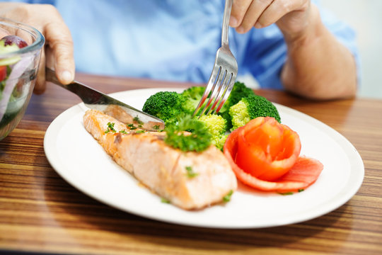 Asian senior or elderly old lady woman patient eating salmon breakfast healthy food with hope and happy while sitting and hungry on bed in hospital.