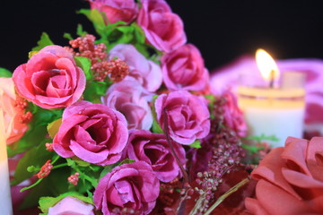 Photoshoot of beautiful bouquet roses with candle burning. Background Valentine day