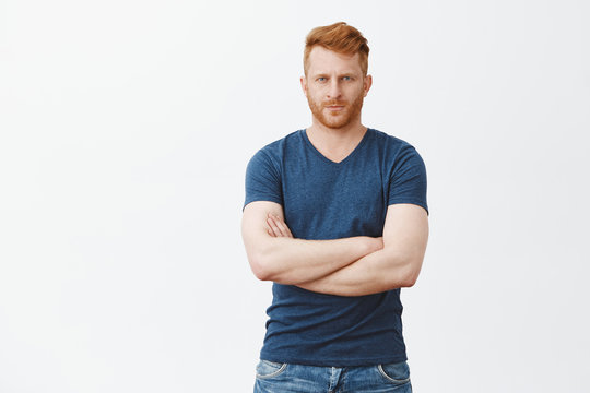Good-looking serious male bodyguard with red hair and bristle, frowning, looking from under forehead strict at camera, crossing fingers on chest, being strong and masculine, posing over gray wall
