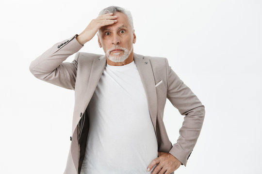 Portrait of nervous senior businessman in suit touching forehead holding hand on waist and holding breath feeling troubled and concerned facing problem standing worried and anxious over white wall