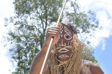 Unrecognizable Torres Strait Islander man dancing traditional dance in Torres Strait Islands near Australia's Cape York Peninsula and the island of New Guinea.