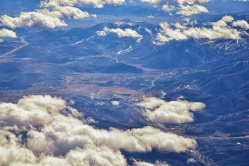 Aerial view of topographical Rocky Mountain landscapes on flight over Colorado and Utah during winter. Grand sweeping views of rivers, mountain and landscape patterns. Top view, Rockies and Wasatch Fr